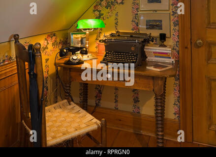 Antique desk and chair in the upstairs guestroom of an old 1977 reconstructed Canadiana cottage style log home - Stock Photo