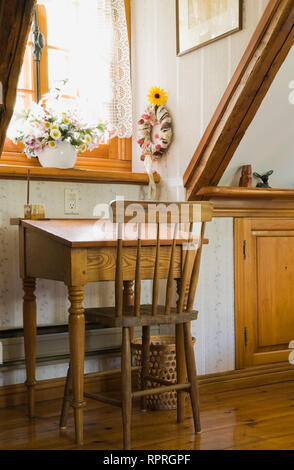 Antique school desk and chair in an upstairs bedroom of an old 1983 reconstructed cottage style log home - Stock Photo