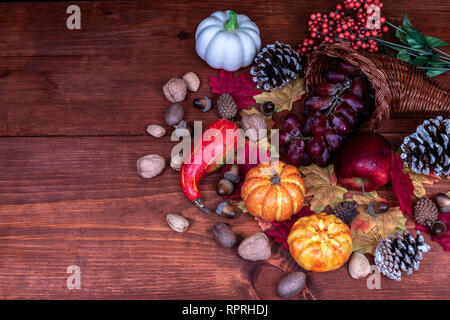 Thanksgiving decor with  frosted pine cones, sunflowers, acorns, pumpkins, grapes, apple, squash, guard, berries and maple leaves - Stock Photo
