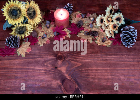 Thanksgiving decor with candle, frosted pine cones, sunflowers, acorns and maple leaves - Stock Photo