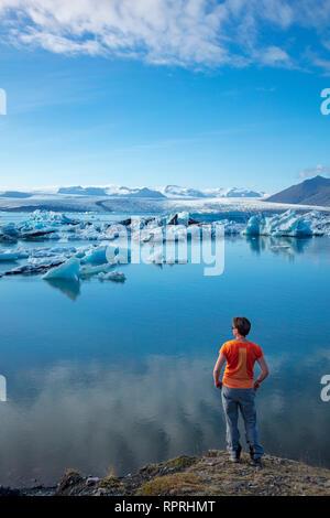 Person on the shore of Jokulsarlon glacier lagoon, beneath Vatnajokull glacier. Vatnajokull National Park, Sudhurland, south east Iceland. - Stock Photo