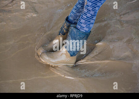 Muddy wellies in a muddy puddle, Sussex, UK - Stock Photo