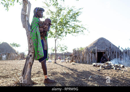 Zemba woman with child in the morning in a village near Epupa Falls, Kunene, Namibia, Africa - Stock Photo