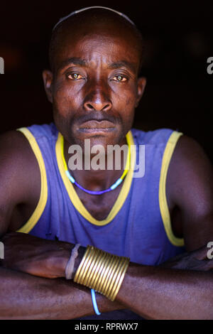 Portrait of a Hakaona (Zemba) man with traditional ornaments and hairstyle. Namibia, Africa - Stock Photo