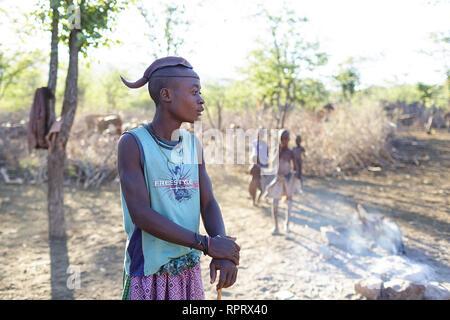 Himba boy in a village near Epupa Falls, Kunene, Namibia, Africa - Stock Photo