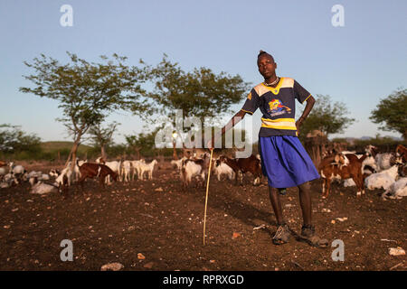 Himba boy looking after the goats in a village near Epupa Falls, Kunene, Namibia, Africa - Stock Photo