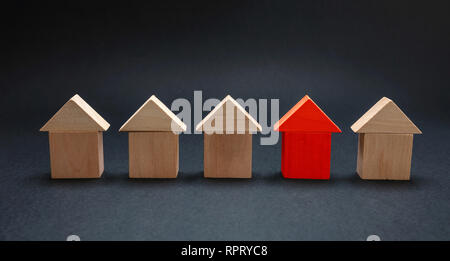 House choice, selection, property and real estate concept. Red house model among wooden houses, black color background - Stock Photo