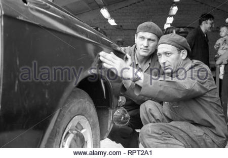 This is Soviet car maintenance station. Car mechanics replaced the wing on the car, which had the road accident. Now they are looking at whether the item is correctly installed. The owner of the car stands next with child on his arms. He's monitoring the progress. The station worker is talking to him. - Stock Photo
