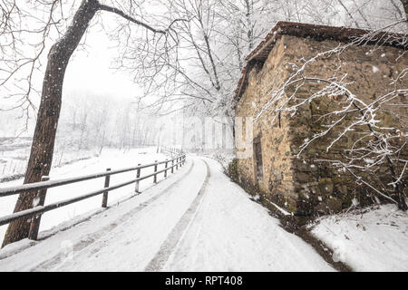 Snow along the road to the Abbey of San Pietro in Vallate, Piagno, Sondrio province, Valtellina, Lombardy, Italy - Stock Photo