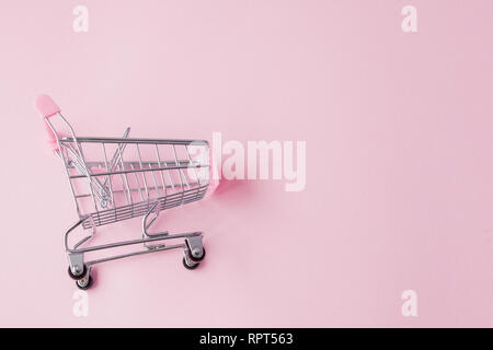 Small supermarket grocery push cart for shopping toy with wheels and pink plastic elements on pink pastel color paper flat lay background. Concept of  - Stock Photo