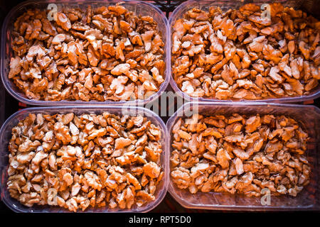Four plastic recycled containers full of peeled delicious walnuts ready to be eaten - Stock Photo