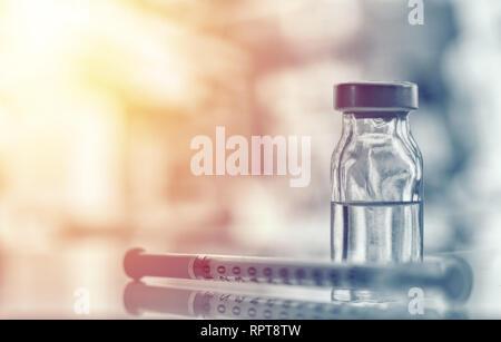 Closeup of medicine vial or flu, measles vaccine bottle with syringe and needle for immunization on vintage medical background, medicine and drug conc - Stock Photo