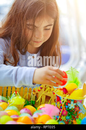 Portrait of a cute little girl playing with colorful eggs, painting and decorating, traditional Easter fun, religious holiday - Stock Photo