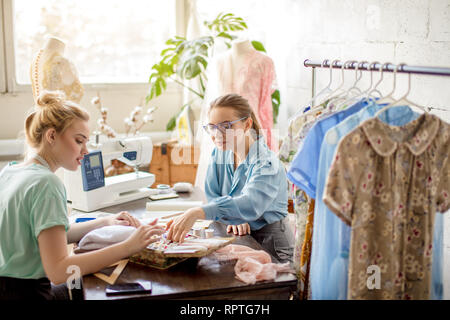 Two female fashion designers working together at workplace at workshop for sewing clothes, brainstorming over new dress designs. - Stock Photo