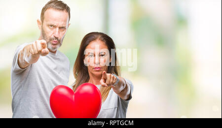 Middle age hispanic casual couple in love holding red heart over isolated background pointing with finger to the camera and to you, hand sign, positiv - Stock Photo