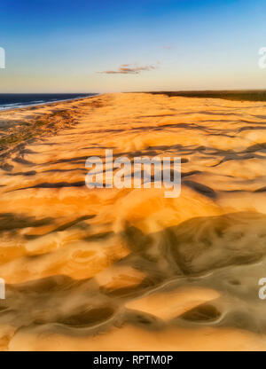 Sun lit sand dunes on Stockton beach of Australia in vertical aerial panorama from top down view to land surface up to distaint horizon and Newcastle. - Stock Photo