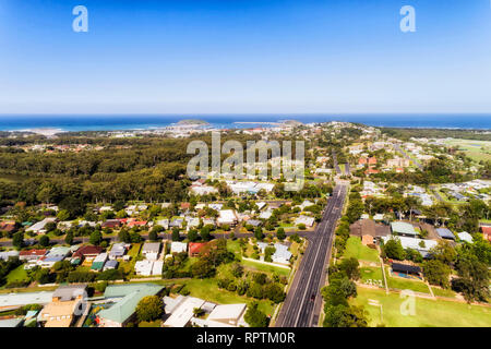 Aerial view over local regional town Coffs Harbour on Australian Middle North Coast of NSW towards Pacific ocean waterfront over local suburbs, street - Stock Photo