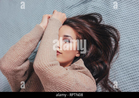 Happy smiling beautiful long hair asian girl young woman in cozy beige sweater lying on blue knitted blanket - Stock Photo