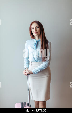 Cute business woman with long red hair, dressed in formal manner, just landing from airplane trip, posing with pink baggage bag, against grey backgrou - Stock Photo