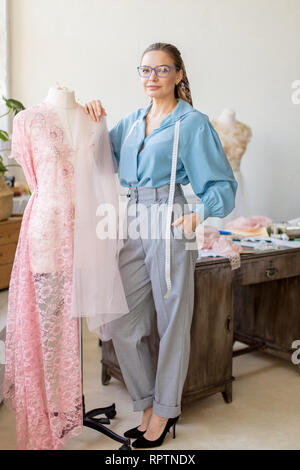 Creative female seamstress wearing eyeglasses, dressed in elegant blouse and straight pants with measuring tape smiling pleasantly working with dummy  - Stock Photo