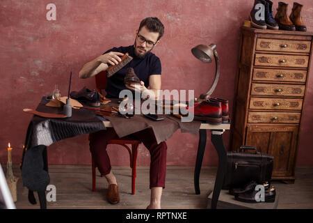 pleasant shoeshine man polishing elegant footwear indoors. full length photo - Stock Photo