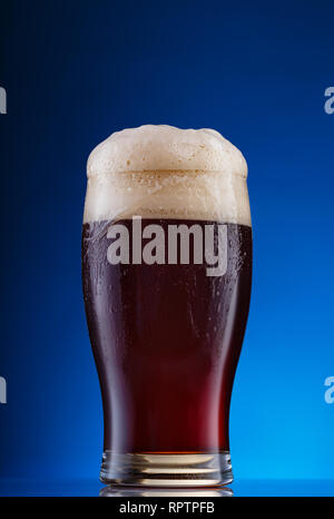Glass of dark beer with foam on blue background - Stock Photo