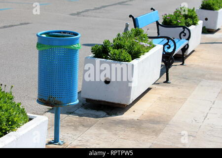 Blue metal public trash can with new plastic bag in same row with blue wooden public bench with black iron frame and white concrete flower pots - Stock Photo