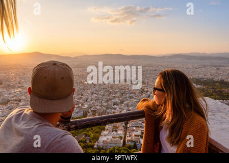 ATHENS, GREECE - September 13, 2018: A couple watching Athens from the Lycabettus hill at sunset time. - Stock Photo