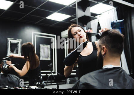 Master cuts hair and beard of men in the barbershop, hairdresser makes hairstyle for a young man. - Stock Photo