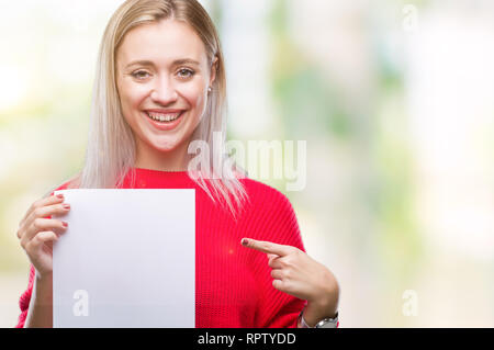 Young blonde woman holding blank paper sheet over isolated background very happy pointing with hand and finger - Stock Photo