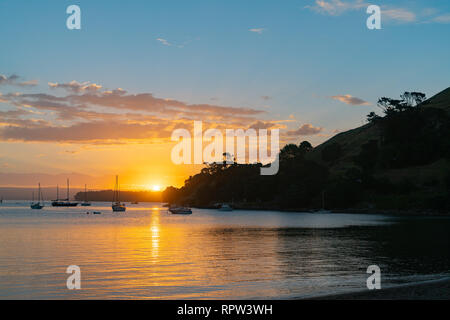 Scenic vista as sun sets over Pilot Bay on Tauranga Harbour with silhouette of boats and Mount Maunganui - Stock Photo