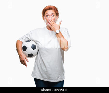 Atrractive senior caucasian redhead woman holding soccer ball over isolated background cover mouth with hand shocked with shame for mistake, expressio - Stock Photo
