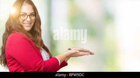 Beautiful plus size young business woman wearing elegant jacket and glasses over isolated background Pointing to the side with hand and open palm, pre - Stock Photo