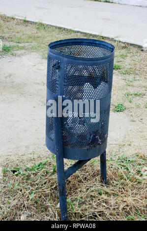 small black metal garbage container or urn on the street - Stock Photo