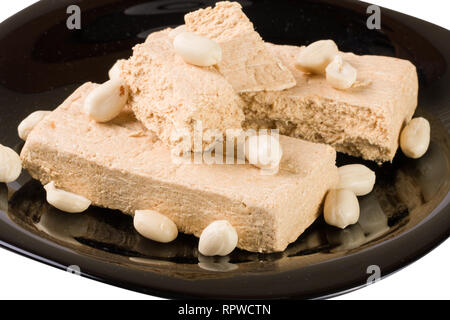peanut halva on a black plate isolated on white background - Stock Photo
