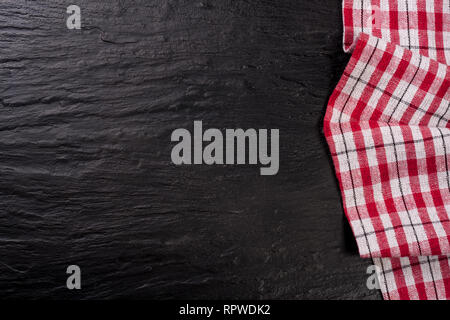 Red checkered tablecloth on a dark stone background with copy space for your text. Top view - Stock Photo