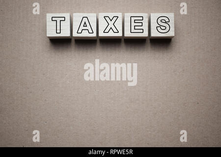 Tax concept with wooden blocks on table - Stock Photo