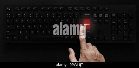 Hand pressing start button on computer keyboard - Stock Photo
