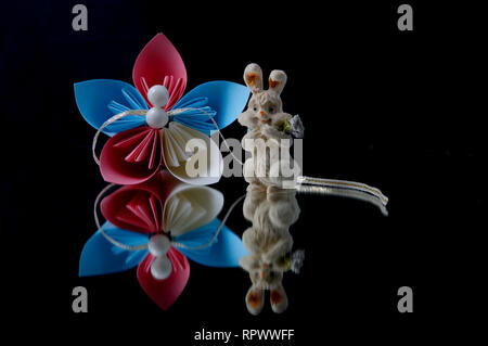 Self made paper flower and ceramic easter bunny on a black background - Stock Photo