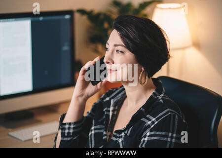 pretty young woman having a business call in a home office - Stock Photo