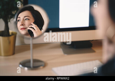 reflection of an attractive female freelancer in a makeup mirror, working from home, talking to her mobile phone. - Stock Photo