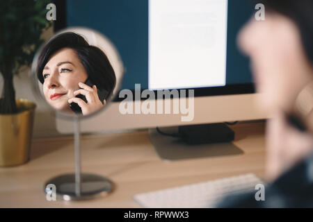 reflection of a female businesswoman in a cosmetic mirror, talking on her mobile phone and working from a home office. - Stock Photo
