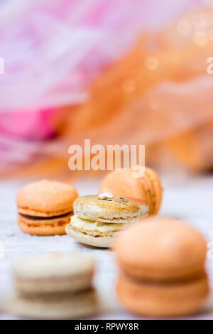 Orange macaroons with chocolate filling and Easter bunny macaroons, on orange tulle background - Stock Photo