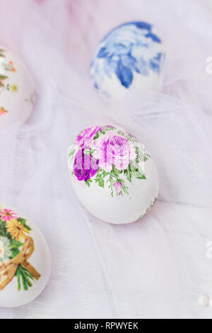 Decorated Easter eggs and flowers on white tulle background; decoupage technique - Stock Photo