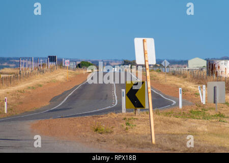 Endless straight road through dry farmland in the Australian Outback - Stock Photo