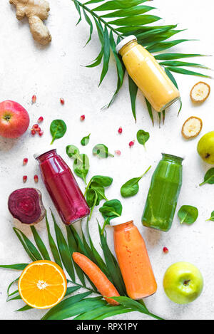 Various smoothies or juices in bottles and ingredients on white, healthy diet detox vegan clean food concept, top view, copy space. - Stock Photo