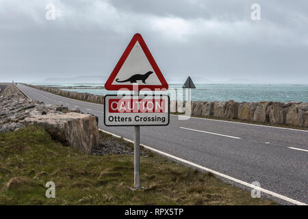 'Caution Otters Crossing' road sign on the approach to the causeway from South Uist to Eriskay, Outer Hebrides, Scotland. - Stock Photo