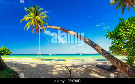 Tropical beach with scenery wooden swing on palm tree on background crystal clear sea water and blue summer sky