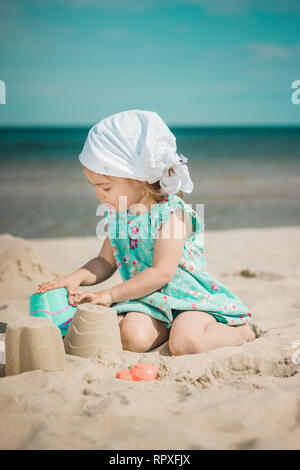 Young girl in sundress making sandcastles on sunny beach. - Stock Photo