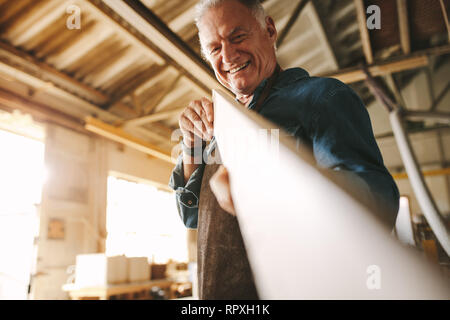 Senior carpenter checking if the board is flat and even. Carpenter measures wood, checking it for straightness while preparing part for furniture. - Stock Photo